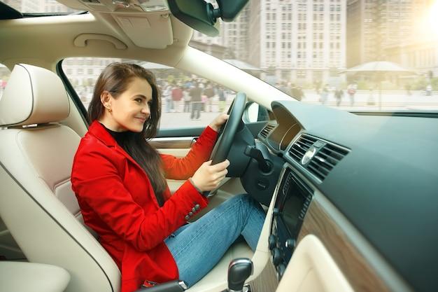Durch die stadt fahren. junge attraktive frau, die ein auto fährt. junges hübsches kaukasisches modell in der eleganten stilvollen roten jacke, die am modernen fahrzeuginnenraum sitzt.