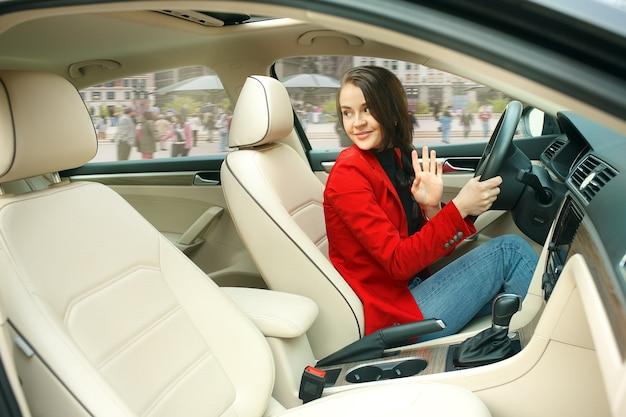 Durch die stadt fahren. junge attraktive frau, die ein auto fährt. junges hübsches kaukasisches modell in der eleganten stilvollen roten jacke, die am modernen fahrzeuginnenraum sitzt