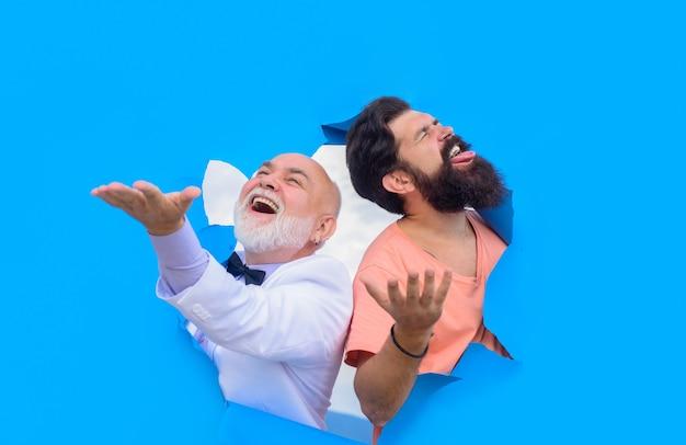Durch papier-emotionen machen männer ein loch im papierwerbungserfolg, erfolgreiche männer schauen durch das loch