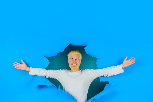 Durch papierwerbung emotionen rabatt verkauf saisonverkauf glücklicher bärtiger mann, der aus papier späht