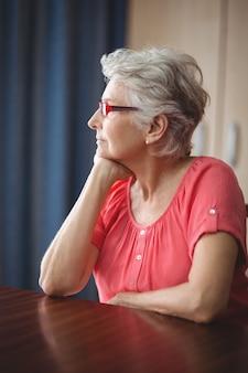 Durchdachte ältere frau, die an einem tisch sitzt