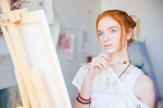 Durchdachte attraktive junge malerin, die mit pinsel vor staffelei steht und in der kunstwerkstatt träumt