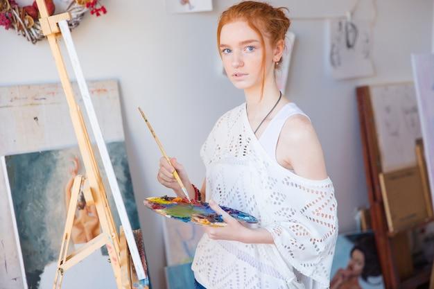 Durchdachte attraktive junge malerin, die ölfarben zum malen auf leinwand in der kunstwerkstatt verwendet