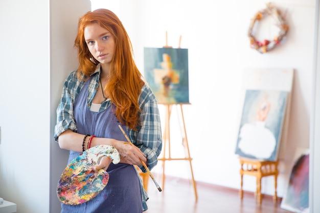 Durchdachte attraktive junge malerin mit langen roten haaren in schürze mit kunstpalette und pinsel in der künstlerwerkstatt