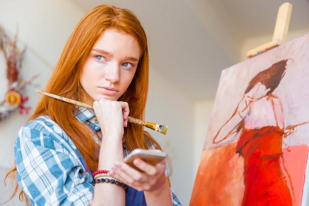 Durchdachte attraktive junge malerin mit lesekopf, die in der künstlerwerkstatt ein handy denkt und hält