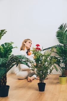 Durchdachte frau, die auf boden mit blumen nahe grünpflanzen sitzt