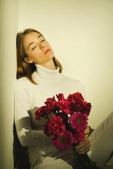 Durchdachte frau, die mit blumenblumenstrauß sitzt