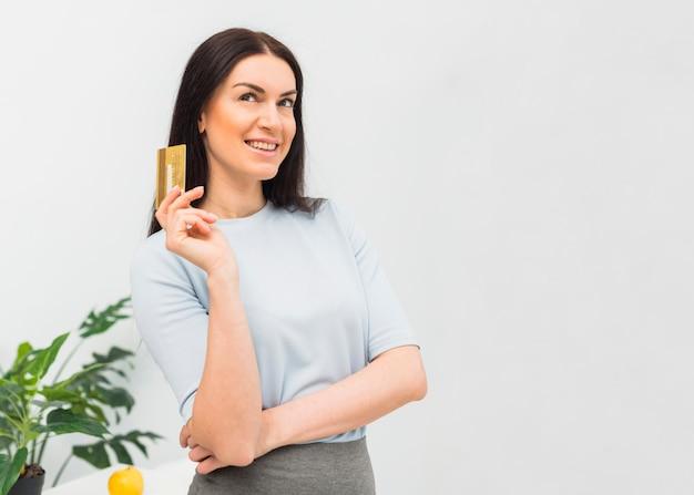 Durchdachte frau, die mit kreditkarte steht