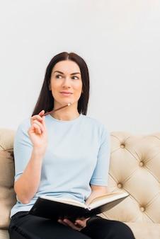 Durchdachte frau, die mit notizbuch und bleistift auf couch sitzt