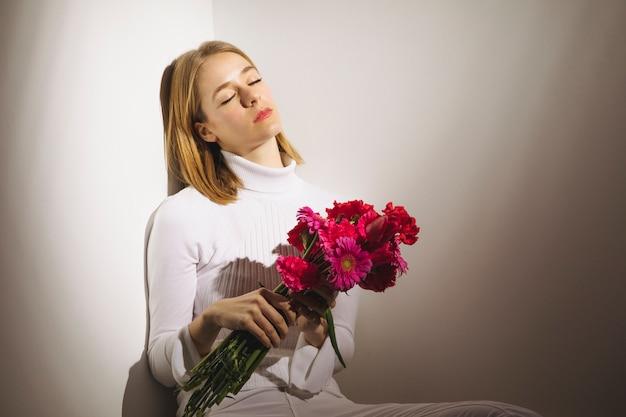 Durchdachte frau, die mit rosa blumenblumenstrauß sitzt