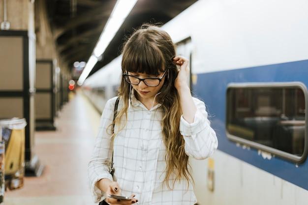 Durchdachte frau, die zu musik beim warten auf einen zug an einer u-bahnplattform auflistet