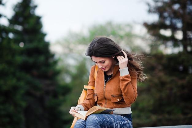 Durchdachte frau erwägt über buch, das sie während ihrer ferien der freizeit im frühjahr liest, die herrliche junge frau, die etwas träumt, das beim sitzen am herbstpark gut ist