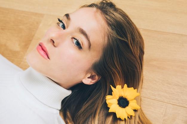 Durchdachte frau mit gelber blume im haar, das auf fußboden liegt