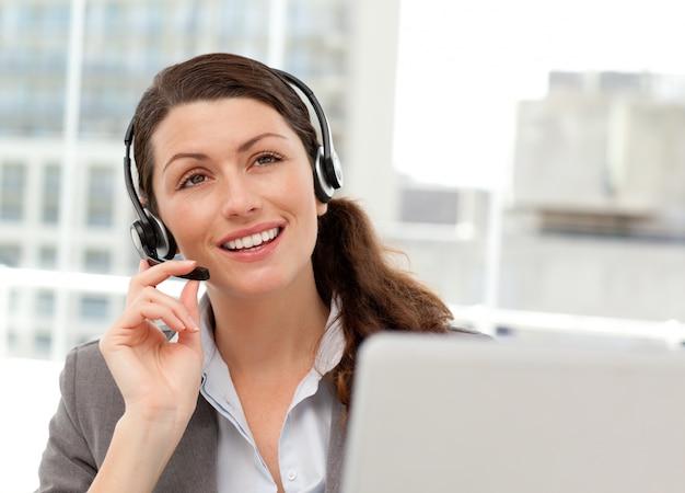 Durchdachte geschäftsfrau, die am telefon beim arbeiten an ihrem computer spricht
