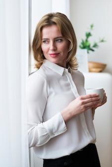 Durchdachte geschäftsfrau, die mit kaffeetasse steht