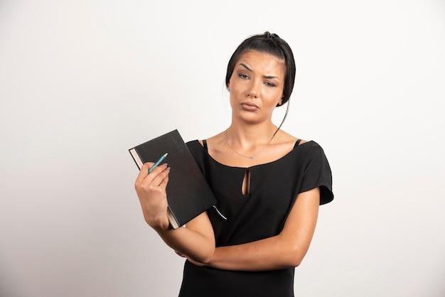 Durchdachte geschäftsfrau, die mit notizbuch auf weißer wand aufwirft.