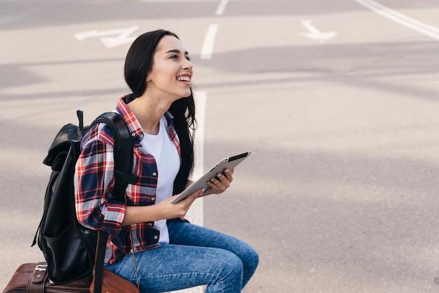 Durchdachte glückliche frau, die digitale tablette hält und über gepäcktasche auf straße sitzt