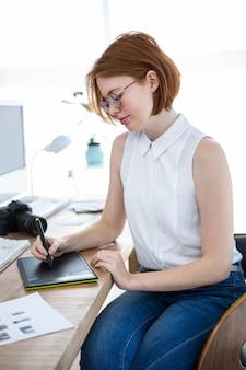 Durchdachte hippie-geschäftsfrau, die an ihrem schreibtisch mit einem digitalen zeichentablett sitzt