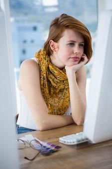Durchdachte hippie-geschäftsfrau, die auf ihren computer sich konzentriert