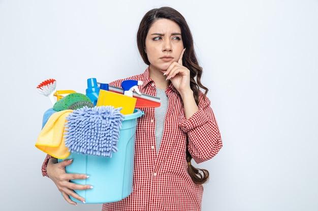 Durchdachte hübsche kaukasische putzfrau, die reinigungsgeräte hält und die hand auf ihr kinn legt und auf die seite schaut