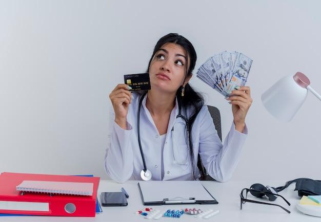 Durchdachte junge ärztin, die medizinische robe und stethoskop trägt, sitzt am schreibtisch mit medizinischen werkzeugen, die geld und kreditkarte halten, die seite lokalisiert betrachten