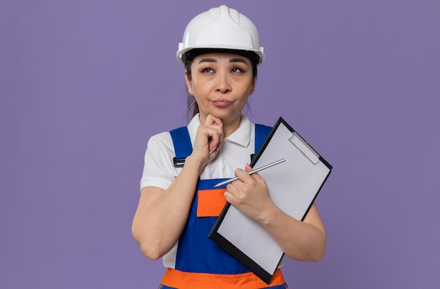 Durchdachte junge asiatische baumeisterin mit weißem schutzhelm, die zwischenablage hält und nach oben schaut
