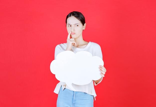 Durchdachte junge frau, die ideentafel in einer wolkenform hält