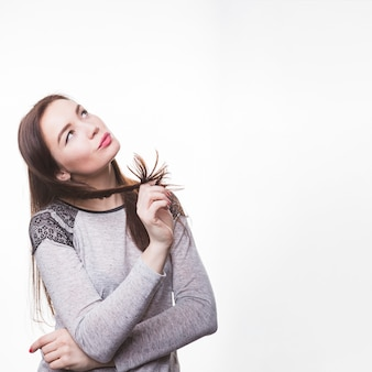 Durchdachte junge frau, die ihr brunettehaar wirbelt