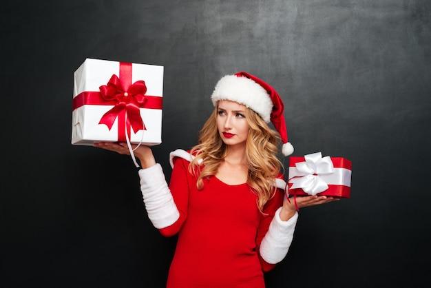 Durchdachte junge frau im weihnachtsmann-kostüm, die geschenk über schwarzer oberfläche steht und wählt