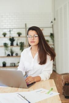 Durchdachte junge frau in intelligenter freizeitkleidung, die beim sitzen im büro arbeitet. porträt einer jungen frau, die an einem laptop arbeitet. kleinunternehmen und unternehmen.