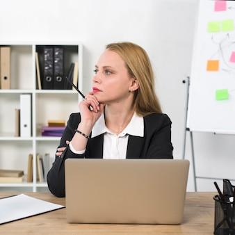Durchdachte junge geschäftsfrau, die am arbeitsplatz mit laptop auf tabelle sitzt