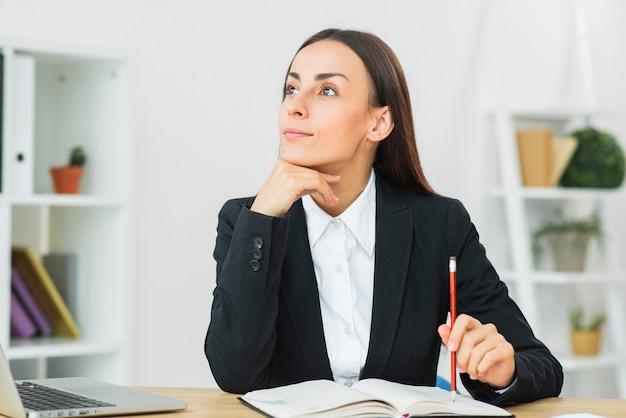 Durchdachte junge geschäftsfrau, die bleistift auf tagebuch über dem schreibtisch hält
