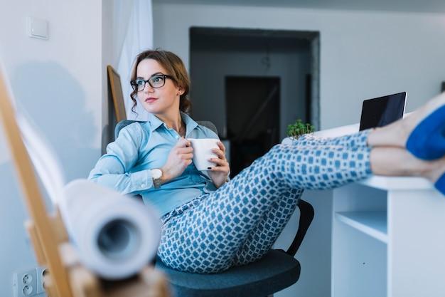 Durchdachte junge geschäftsfrau, die kaffeetasse sich entspannt auf einem bürostuhl hält