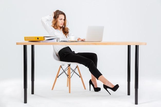 Durchdachte junge geschäftsfrau, die mit laptop auf weißem hintergrund denkt und arbeitet