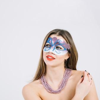 Durchdachte junge lächelnde Frau in tragender Halskette der Maskeradekarnevalsmaske