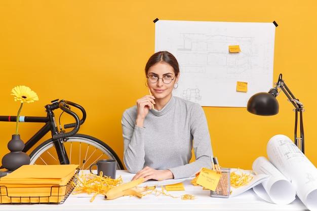 Durchdachte kreative arbeiterin träumt von urlaub, während sie im büro arbeitet, entwickelt neues geschäftsprojekt macht blaupausen trägt brillen posiert im coworking space analysiert informationen.
