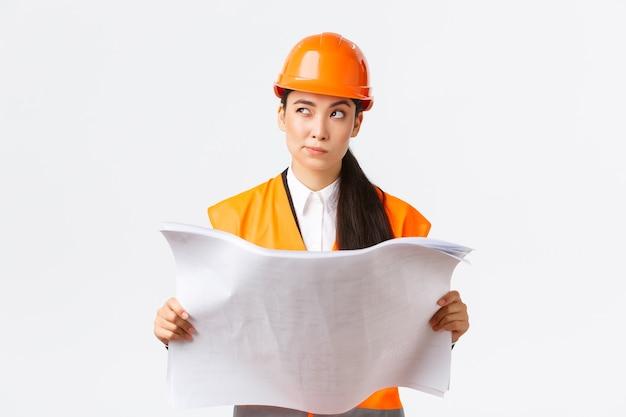 Durchdachte professionelle asiatische bauleiterin, architektin, die blaupausen liest und wegschaut, nachdenkt, nachdenkt, entscheidungen trifft, während sie den projektplan studiert, weißer hintergrund