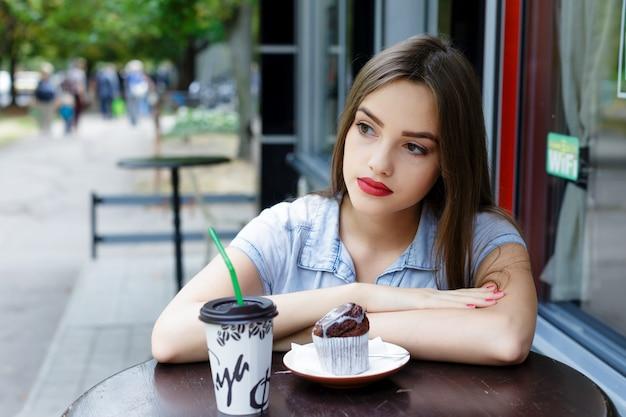 Durchdachte schöne junge frau im café im freien mit kaffee und muffin