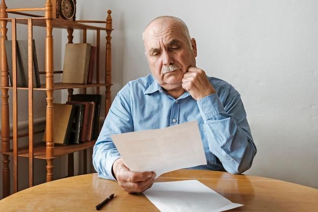 Durchdachter alter mann, der ein papierdokument liest
