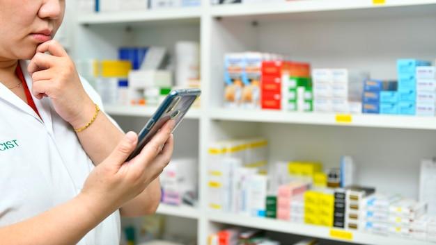 Durchdachter apotheker, der ein mobiles smartphone zum ausfüllen eines rezepts in der apotheke hält