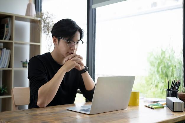 Durchdachter designer des jungen mannes, der informationen über laptop-computer überprüft.