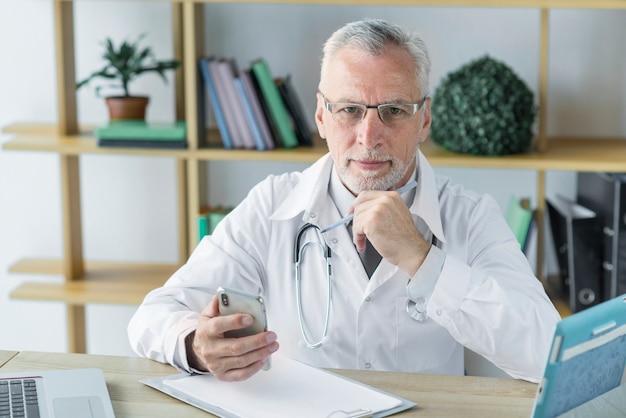 Durchdachter doktor mit smartphone