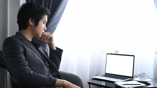 Durchdachter geschäftsmann, der am modernen arbeitsplatz sitzt und laptop-computer betrachtet.