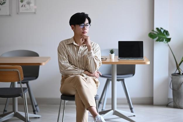 Durchdachter geschäftsmann, der an einem komfortablen arbeitsplatz sitzt und aus dem fenster schaut.