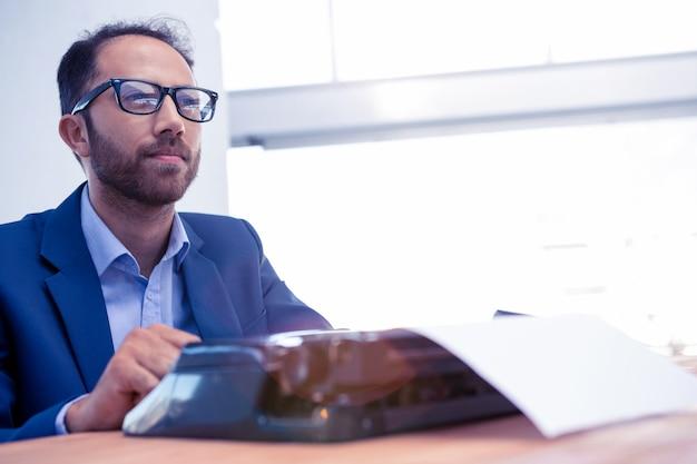 Durchdachter geschäftsmann, der beim arbeiten an schreibmaschine schreibtisch im kreativen büro weg betrachtet