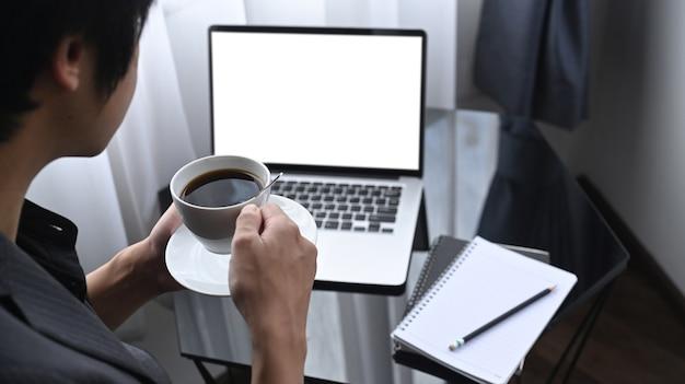Durchdachter geschäftsmann, der kaffee trinkt und laptop im büroraum verwendet.
