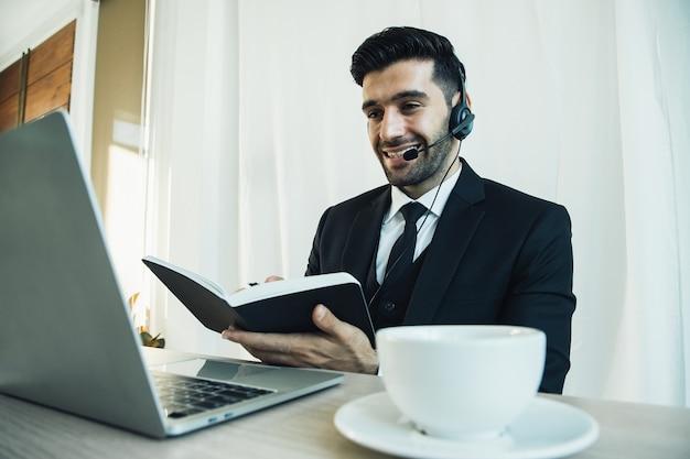 Durchdachter gutaussehender callcenter-geschäftsmann denkt an ein online-projekt mit blick auf den laptop am arbeitsplatz