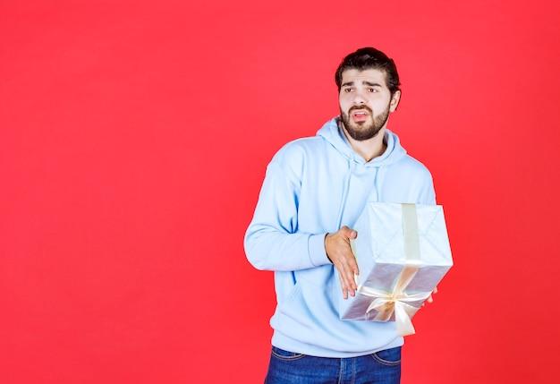 Durchdachter gutaussehender mann, der verpackte geschenkbox hält holding
