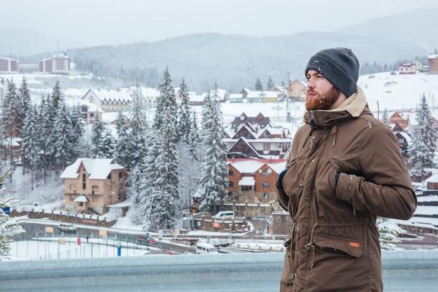 Durchdachter hübscher junger mann, der die aussicht auf das bergresort steht und genießt