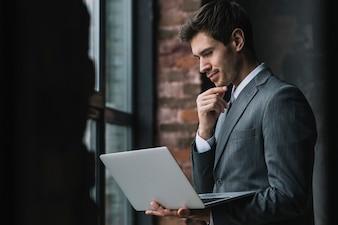 Durchdachter intelligenter junger Geschäftsmann, der Laptop betrachtet